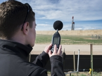 A researcher from CU Denver records noise levels from a oil drill rig in a Greeley, CO neighborhood.